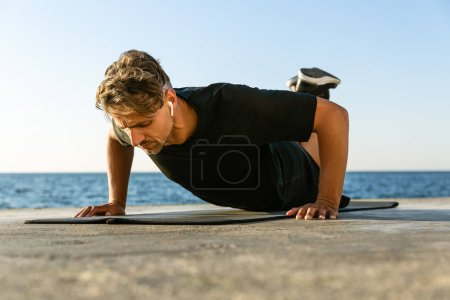 fit adult man with wireless earphones doing push ups on knees on seashore