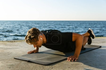 adult sportsman with wireless earphones doing push ups on seashore