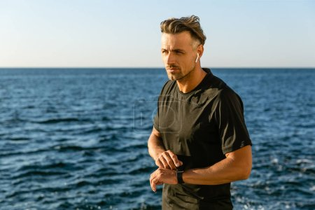 handsome adult man with wireless earphones and smart watch on seashore