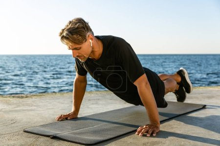 adult sportsman with wireless earphones doing push ups on seashore