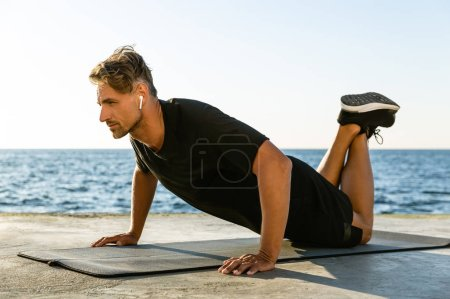sporty adult man with wireless earphones doing push ups on knees on seashore