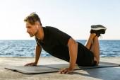 sporty adult man with wireless earphones doing push ups on knees on seashore