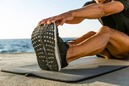 cropped shot of athletic man stretching on seashore