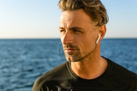 close-up portrait of handsome adult man with wireless earphones on seashore looking away