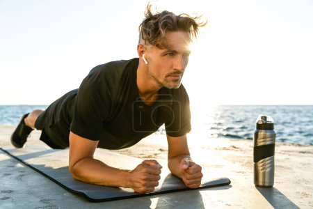 handsome adult sportsman with wireless earphones doing plank exercise on seashore