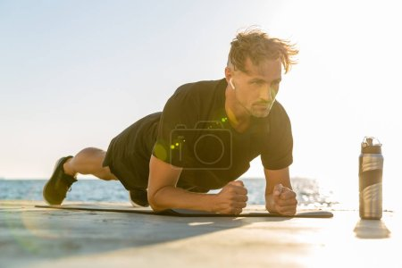 fit adult man with wireless earphones doing plank exercise on seashore