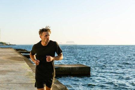 athletic adult man in black sportswear jogging on seashore in morning