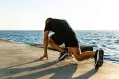 athletic sprint runner in start position for run on seashore