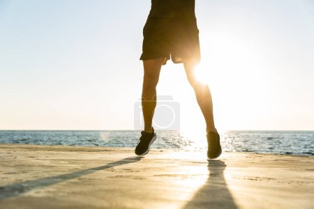 handsome adult sportsman jumping on seashore