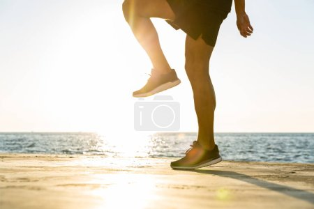 cropped shot of sportsman working out on seashore in front of sunrise