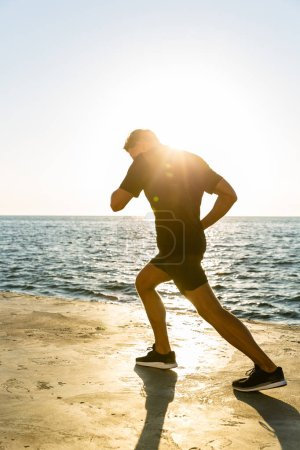 adult sportsman jogging on seashore in front of sunrise