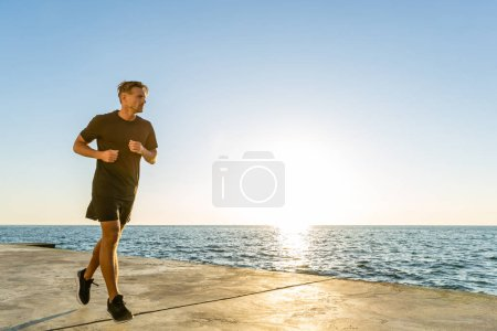 handsome adult sportsman jogging on seashore in front of sunrise