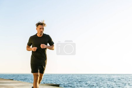 athletic adult joger running on seashore in morning