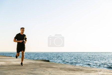 handsome adult sportsman jogging on seashore in morning