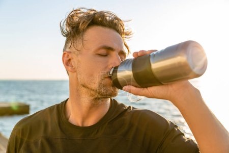 adult sportsman drinking water from fitness bottle on seashore in front of sunrise after workout