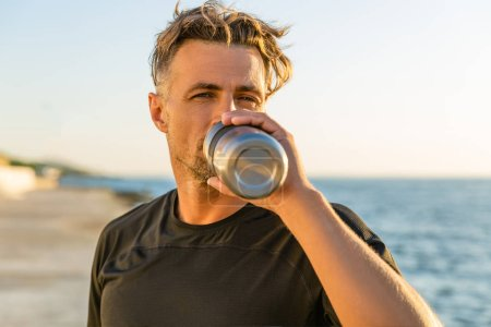 handsome adult man drinking water from fitness bottle on seashore in front of sunrise after training