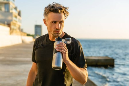 handsome adult sportsman with grey hair holding fitness bottle on seashore in front of sunrise looking away