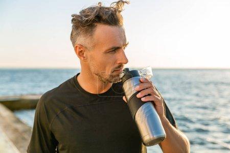 Photo pour Adult sportif avec des cheveux gris, tenant la bouteille de remise en forme sur le bord de la mer en face de lever du soleil à la recherche de suite - image libre de droit