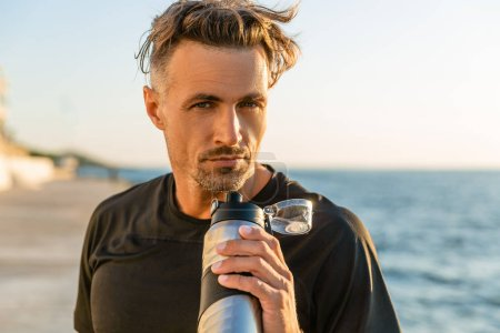 handsome adult man with fitness bottle on seashore in front of sunrise
