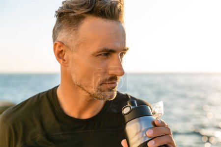 close-up portrait of handsome adult man drinking water from fitness bottle on seashore in front of sunrise