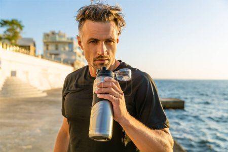 adult sportsman drinking water from fitness bottle on seashore in front of sunrise and looking at camera