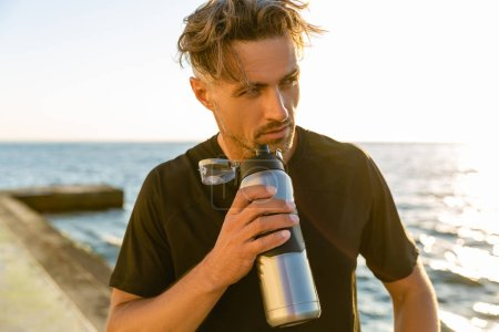 handsome adult man drinking water from fitness bottle on seashore in front of sunrise and looking away