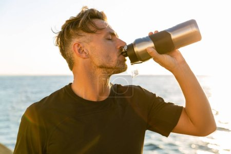 side view of handsome adult man drinking water from fitness bottle on seashore in front of sunrise