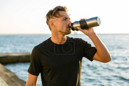 adult sportsman drinking water from fitness bottle on seashore in front of sunrise