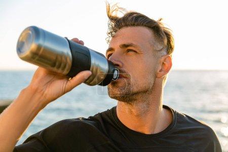 Photo pour Eau potable adulte sportif de bouteille de remise en forme sur le bord de la mer en face de sunrise - image libre de droit