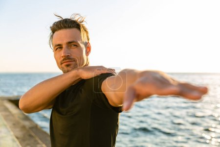 adult sportsman stretching arm before training on seashore