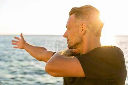 handsome adult sportsman stretching arm before training on seashore in front of sunrise