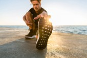 athletic adult man stretching leg on seashore in front of sunrise