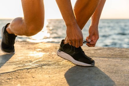 cropped shot of sportsman lacing up sneakers on seashore in front of sunrise