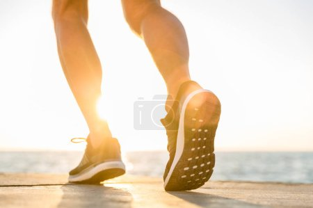 Photo for Cropped shot of sportsman in modern sneakers running by seashore on senrise - Royalty Free Image