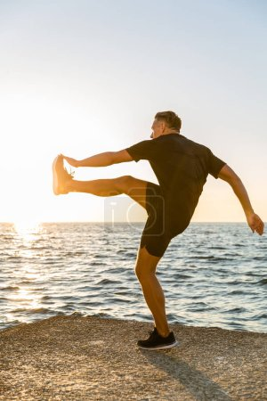 handsome adult sportsman working out on seashore in evening