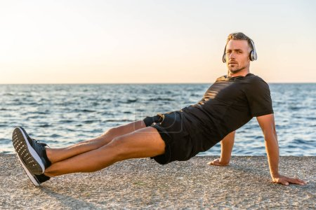 handsome adult sportsman in headphones doing reverse plank and balancing on hands on seashore