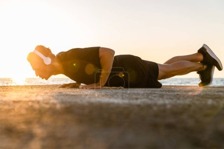 side view of handsome adult sportsman in headphones doing push ups on seashore