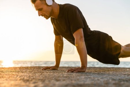 athletic adult man in headphones doing push ups on seashore