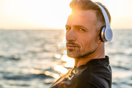 close-up portrait of smiling adult man in wireless headphones looking at camera on seashore in front of sunrise