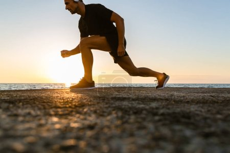 Photo for Side view of handsome adult sportsman doing lunges during training on seashore - Royalty Free Image