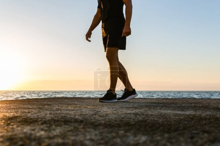 cropped shot of man in modern sportswear standing on seashore