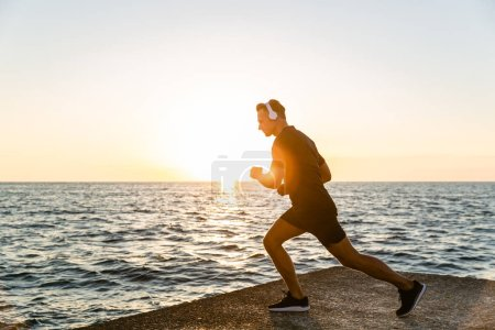 sporty adult man in headphones doing one legged squats during training on seashore