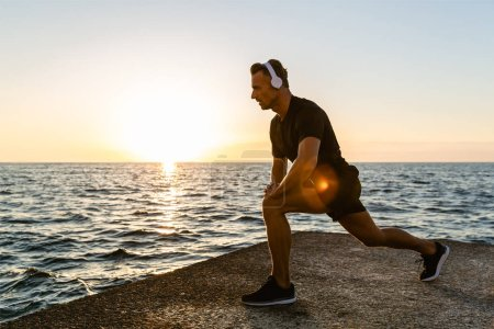 Photo for Athletic adult man in headphones doing one legged squats during training on seashore - Royalty Free Image