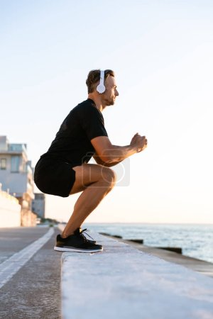 side view of athletic adult man in headphones standing squats on parapet on seashore