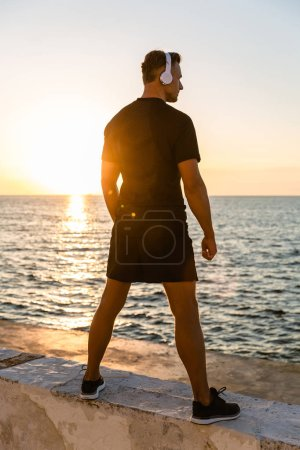 rear view of athletic adult man in headphones standing on seashore in front of sunrise