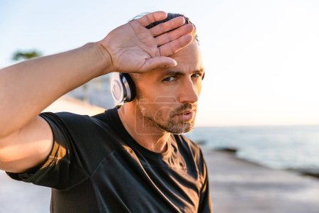 tired fit adult man in wireless headphones wiping forehead with hand on seashore
