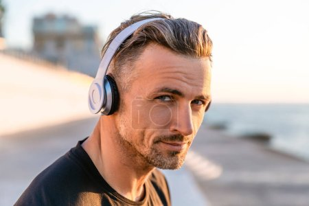 close-up portrait of handsome adult man in wireless headphones looking at camera on seashore