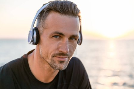 close-up portrait of attractive adult man in wireless headphones looking at camera on seashore
