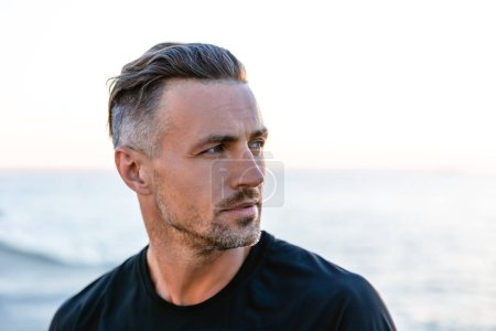 Photo for Close-up portrait of handsome adult man with grey hair looking away on seashore - Royalty Free Image