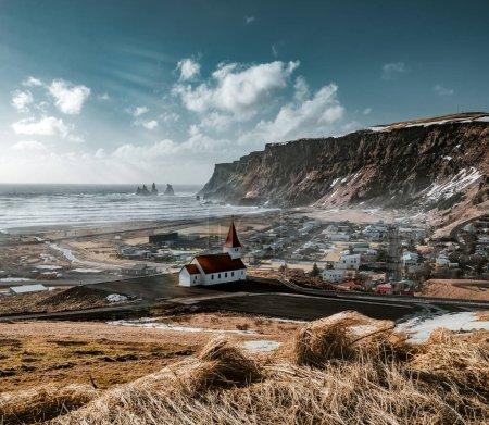 Photo pour Vue panoramique sur le Vik au lever et au coucher du soleil. Sud de l'Islande.Eglise typique en bois de couleur rouge dans la ville de Vik, Islande en hiver.. Photo prise en Islande . - image libre de droit